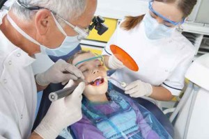 Dentist and dental assistant using ultraviolet light in young pa