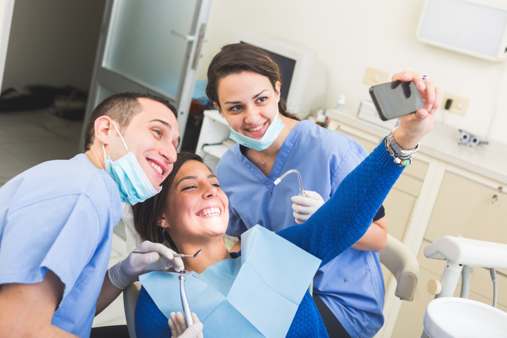 Dentist and Dental Assistant examining Patient teeth.